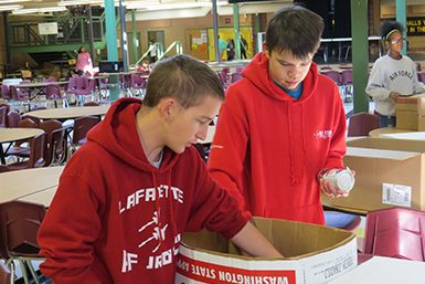 ROTC members help box cans turned in by students in 1st Hour classes.