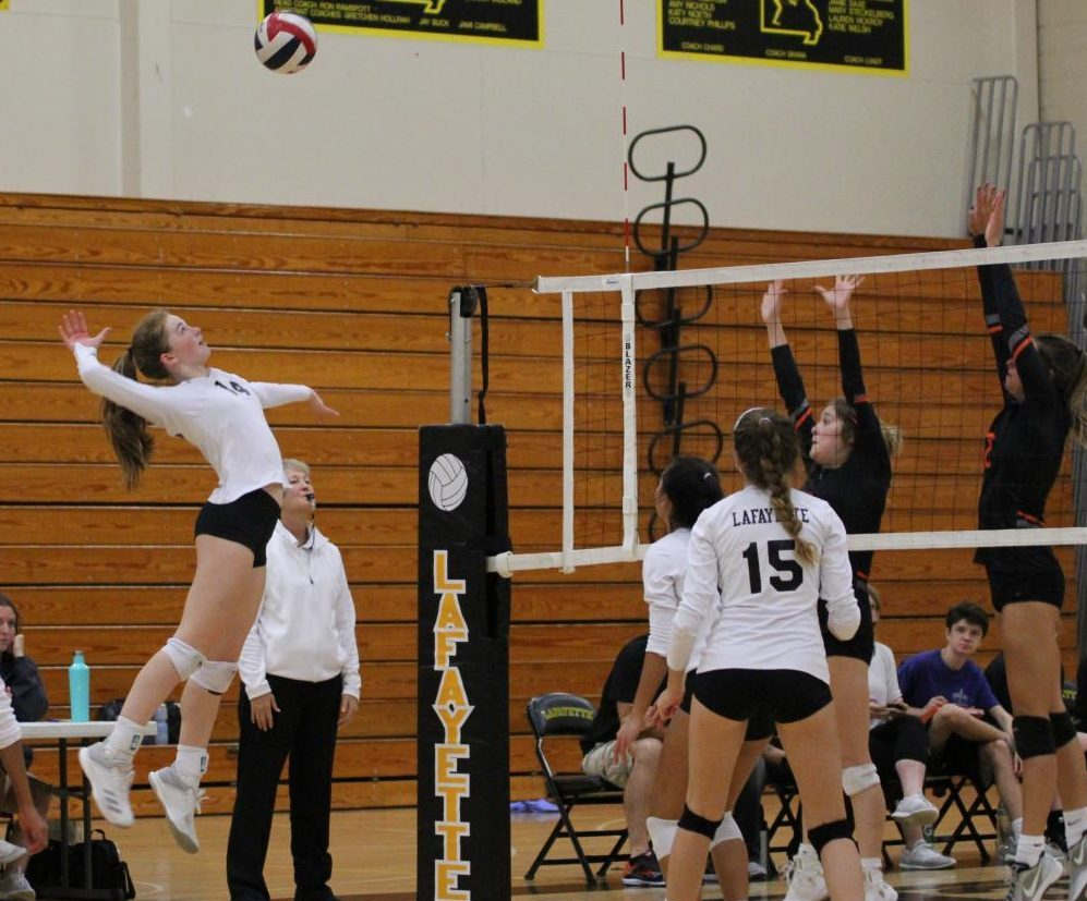 During the Sept. 11 girls volleyball game against Webster Groves, junior Brooke Borgmeyer hits a set from sophomore Jenny Nguyen. Borgmeyer had eight kills in the Lancers' two set victory over the Statesmen. At the conclusion of this week, the girls volleyball team has an overall record of eight wins and three losses.