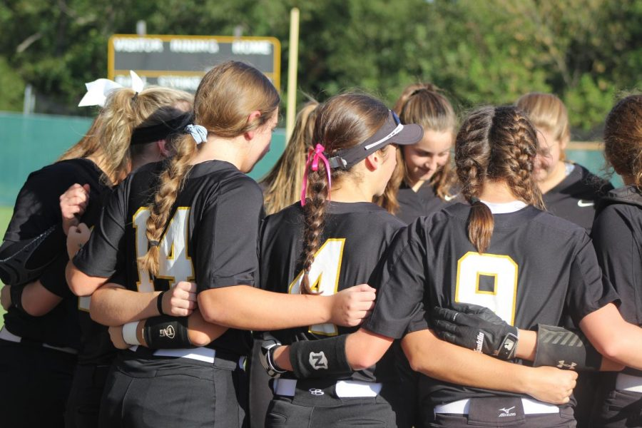 Before a home softball game against Francis Howell North on Oct. 1, the softball team huddles together. The team won 6-0.