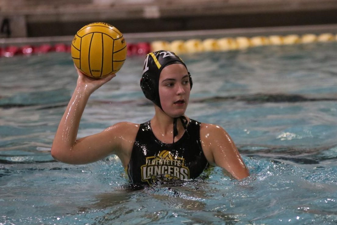 During the March 26 girls water polo game, sophomore Sophie Arceneaux looks to pass to a teammate down the pool.