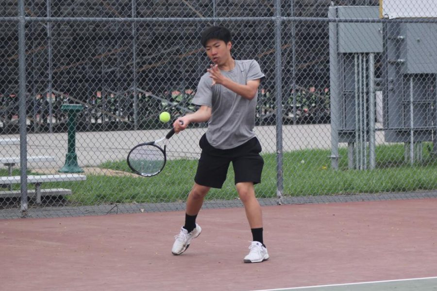 Returning a serve, freshman Merrick Zheng focus on the ball. Zheng was one of two freshmen on the varsity tennis team this year.