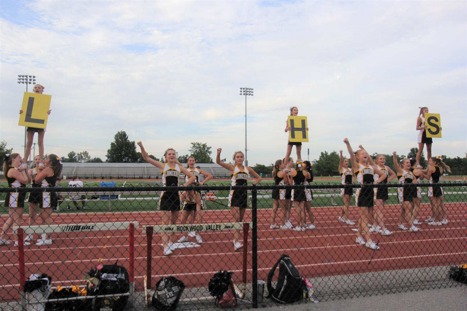 Performing+on+the+track%2C+freshmen+cheerleaders+led+the+event+in+cheering+before+junior+varsity+and+varsity+cheer+performed+later.