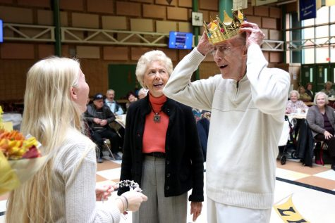 After being named king of the Turkey Dinner Dance, Bruce Hegger places his crown on his head. Hegger attended the event with his friend Vivian Powers, who was named queen.