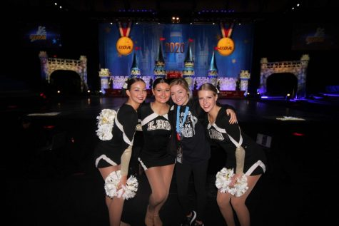 In Feb. 2020, Kennedy Willhite, Natalie Tuttle, coach April Ehrhardt and Leenie Johns all pose in front of the Cinderella Castle set up on the national stage. Johns, along with the rest of the team, traveled to Disney World from Jan. 29-Feb. 4 to compete in the National Dance Team Championship.