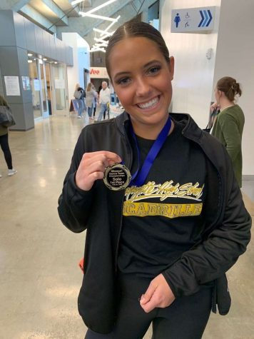 Ainsley Moses holds her medal for 1st place Sophomore Solo at State