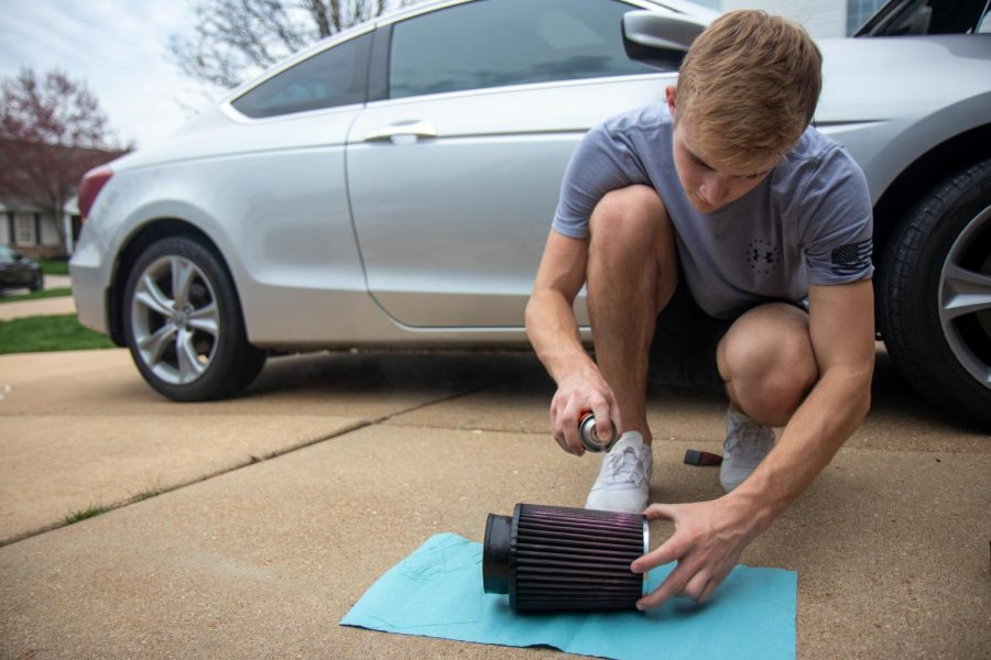 Senior Jake Dederer sprays oil on his cold air intake after cleaning it to pass time while self-quarantined at home, March 27.