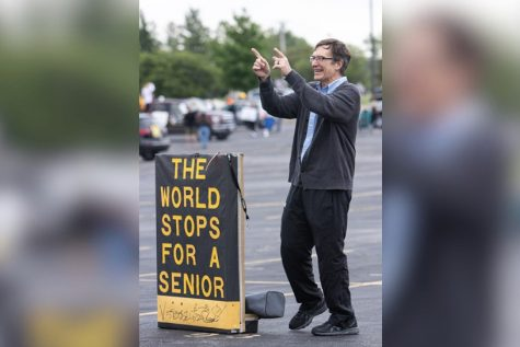 "Retiree Paul Krull. math teacher, congratulates the Class of 2020 at their Farewell Parade on May 21.  He displayed his infamous ""The World Stops for a Senior"" sign."