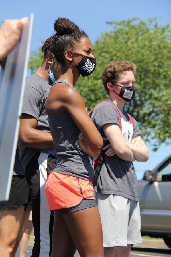 Rising senior Sydney Berry listens to an opening speech during the first part of the peaceful protest.