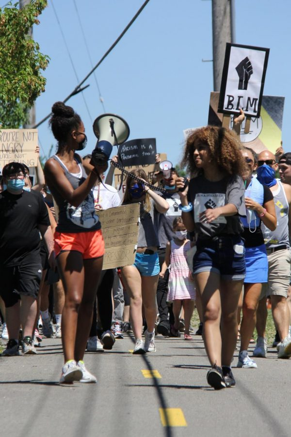 Rising senior Sydney Berry and Class of 2020 graduate Malayka Walton lead the crowd of people that participated in the march along the side of Highway 109.