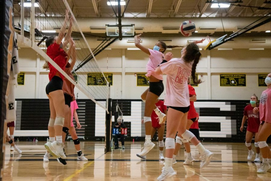 In a scrimmage against other team members, junior Paige Borgmeyer sets up to hit while her teammates attempt to block her. The volleyball team won began their season this week, winning matches against Incarnate Word and Francis Howell.