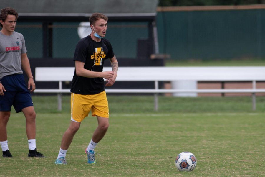 In a practice, boys soccer Head Coach Ryan Butchart demonstrates a play that his team needs to execute. Soccer falls in the medium sport contact, and has now moved on to more active drills and scrimmages at practice.