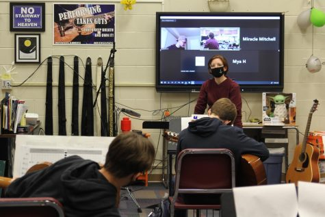 Guitar teacher Traci Bolton simultaneously instructs her in-person students and her online learners during her 4th Hour guitar ensemble class. Unlike in this picture, virtual  students next year will be asynchronous.