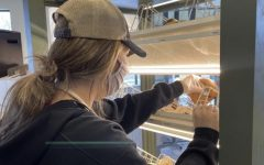Junior Marissa Trottier restocks bagels during her morning shift at St. Louis Bread Company.