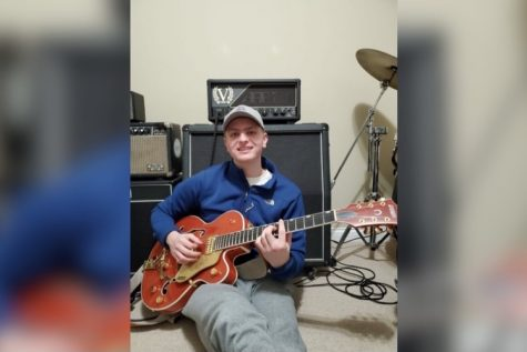 Senior Andrew Arcizewski sits with his Gretsch 6120 guitar, one of eight that he owns.