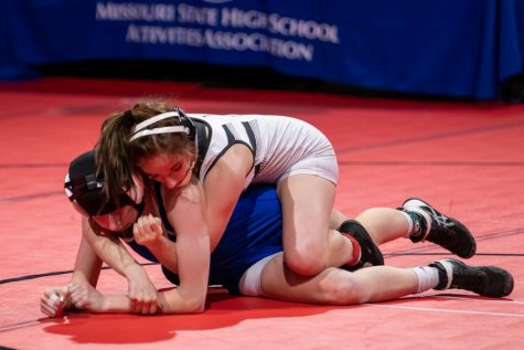 In the State finals, junior Faith Cole holds her opponent down. After this final match Cole won her third straight State title.