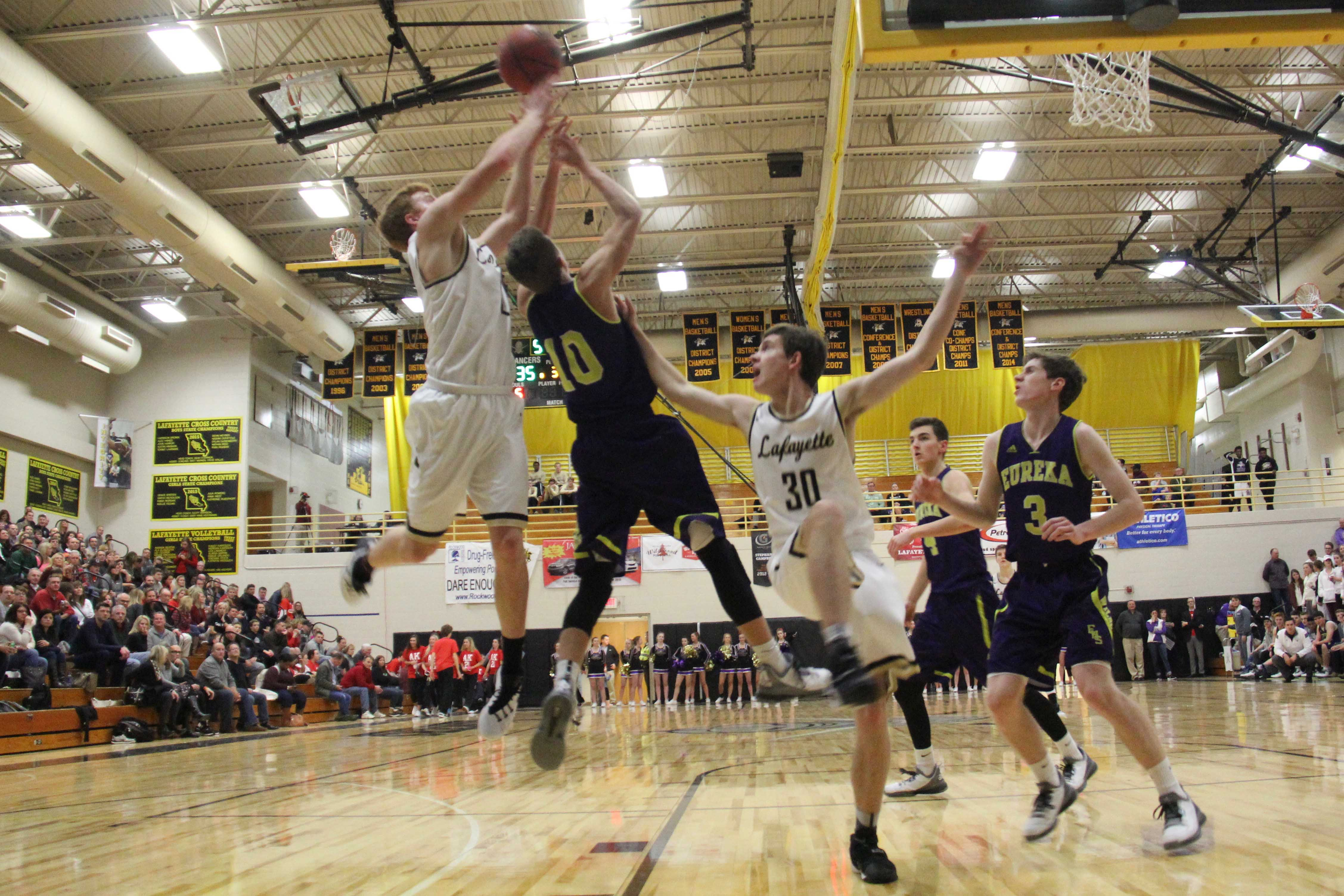 Will Stonecipher (left) fights for a rebound in a game against rival Eureka.
