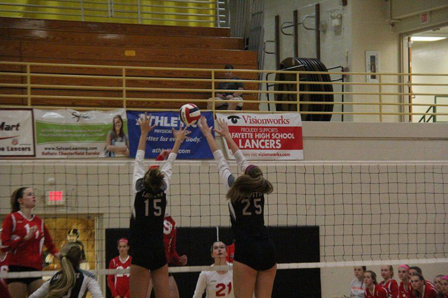 Girls+varsity+volleyball+players+Hannah+Flowers%2C+senior%2C+right%2C+and+Kathryn+Wesolich+block+a+spike+from+Cor+Jesu.