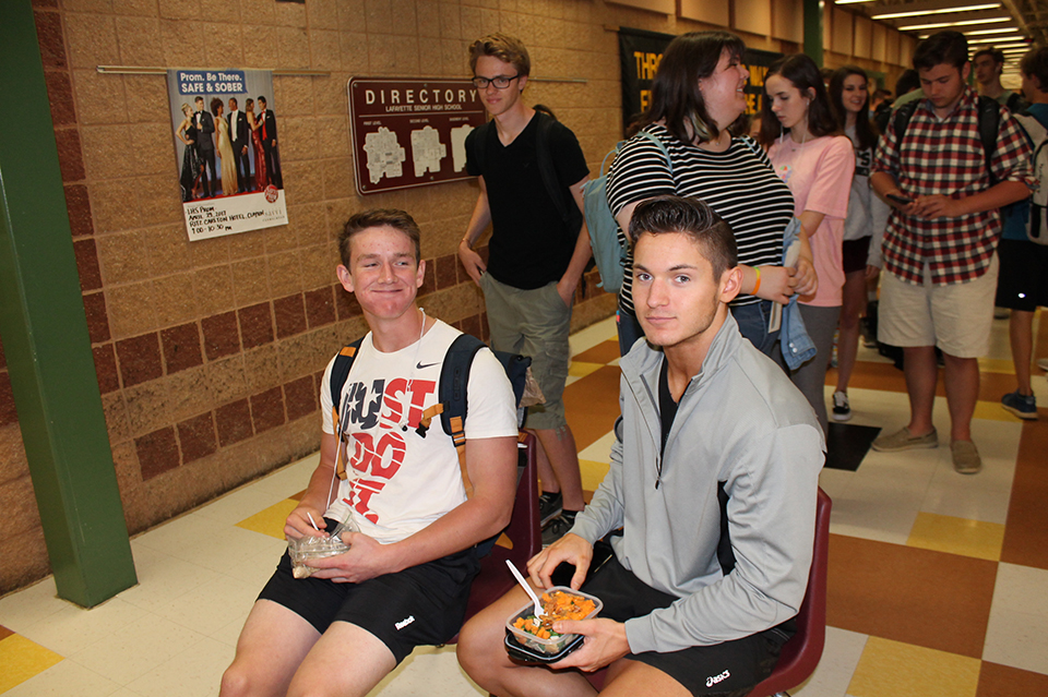 Because of the length of the prom ticket lines, seniors Wade Stauss and Conner Keithly pull up chairs to eat lunch during the wait.