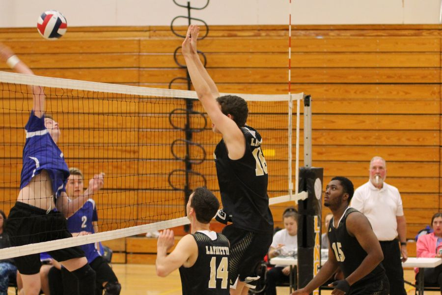 Justin+Houldsworth+jumps+above+the+net+to+block+a+hit+from+a+Northwest+player+last+season.+Houldsworth+was+one+of+the+nine+seniors+on+the+boys+volleyball+team+who+graduated+last+year.+