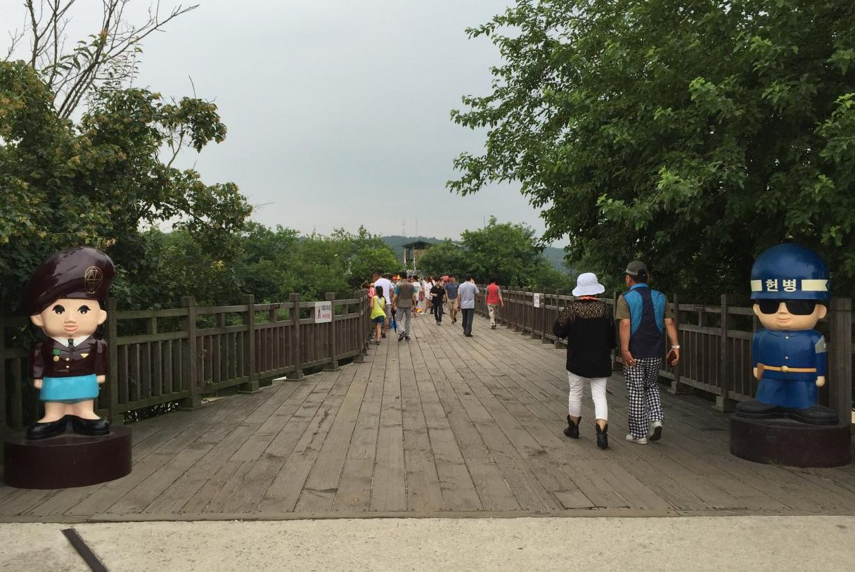 Visitors walk across a bridge in South Korea that borders North Korea. The entrance to the bridge is flanked by North Korean (left) and South Korean (right) soldier figurines.
