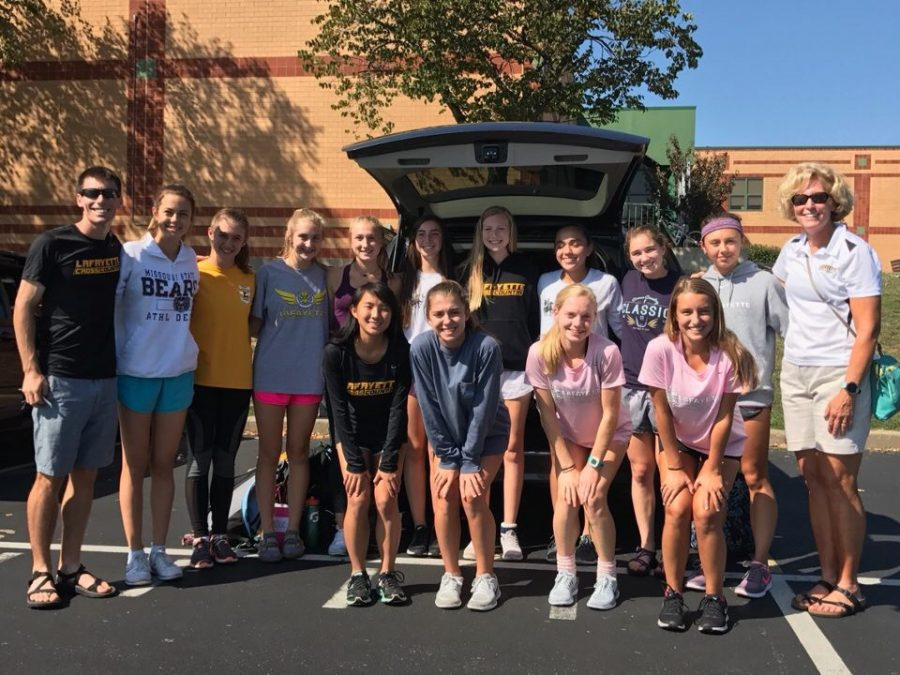 Before traveling to Lawrence, KS, the girls cross country team poses for a picture in front of their rented van. Girls varsity placed 32nd as a team in the substantial race.