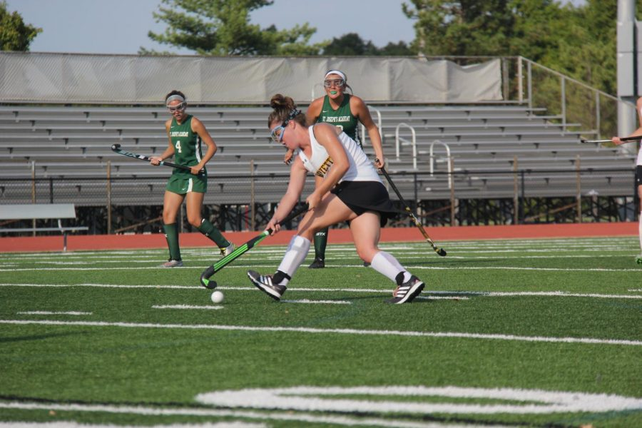 Running past her defenders, senior Meghan Conroy looks for an opportunity to score. Conroy was a big part of the field hockey teams success, scoring a total of 26 goals.
