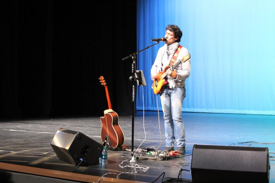 In+the+theater%2C+Javier+Mendoza+sings+one+of+his+songs+for+the+Spanish+class+students+in+attendance.+A+bilingual+artist%2C+Mendoza+performed+original+songs+like+Cinco+M%C3%A1s+and+The+Light%2C+as+well+as+Despacito+by+Luis+Fonsi.+