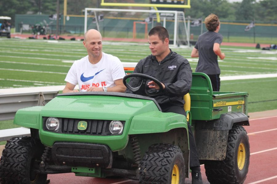 Before the boys soccer game on Aug. 24, Interim Activities Director Jonathon Sumner rides around campus on his gator with cross country coach Matt Warren. This is Sumners first year as the Activities Director.