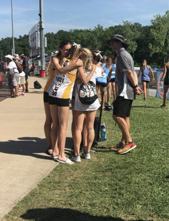 After a long and hot day at the State track meet, the long distance  girls team embraces. The 4x800 meter relay placed 12 out of 16 teams.