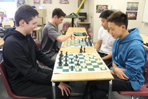 The members of the chess club play chess and forms strategies to win the game.