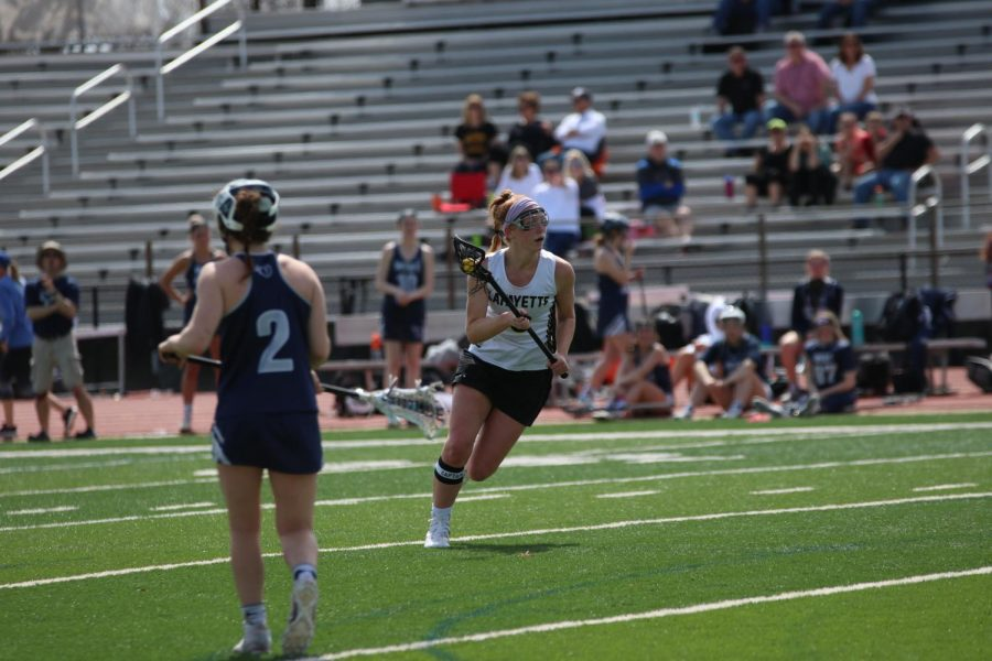 During+a+game+against+Lee%27s+Summit+West%2C+senior+Anna+Reynolds+cradles+the+ball+and+looks+down+the+field.+Reynolds+currently+has+23+goals+on+the+season.+