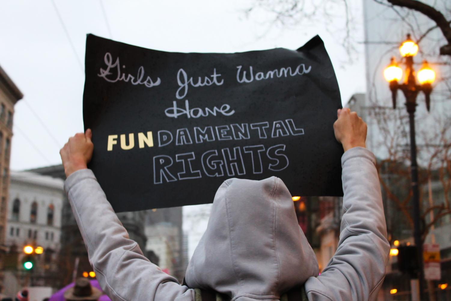 A protester stands in San Francisco's Market Street with a sign reading