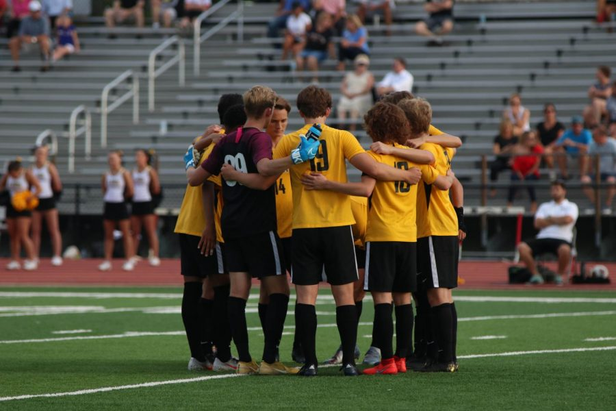 The starting players gather for a pep talk before the game begins. The boys started the game with a 2-1 record.