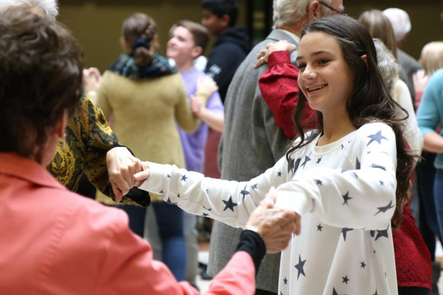 Joining hands with guests, sophomore Grace Rigabar follows along to a dance.