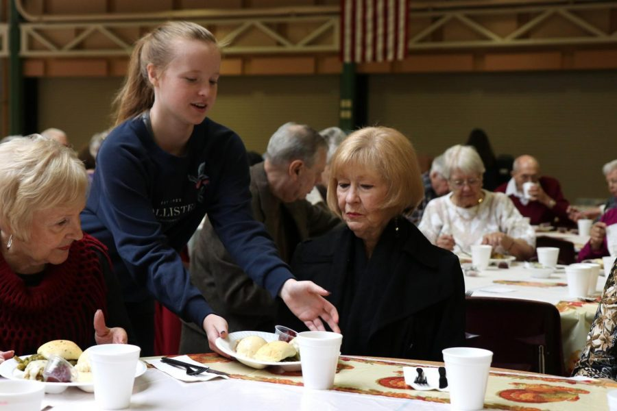 Serving food, junior Kate Barnard hands a plate to a guest. Plates were made up of turkey, green beans, cranberries, stuffing, mashed potatoes and gravy and a roll.