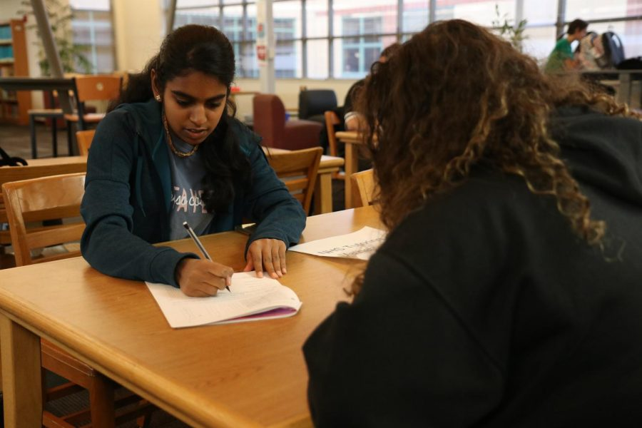 Volunteering for National Honor Society, junior Sneha Manikandan helps freshman Besan Juma complete her math homework on Dec. 13 in the Library.