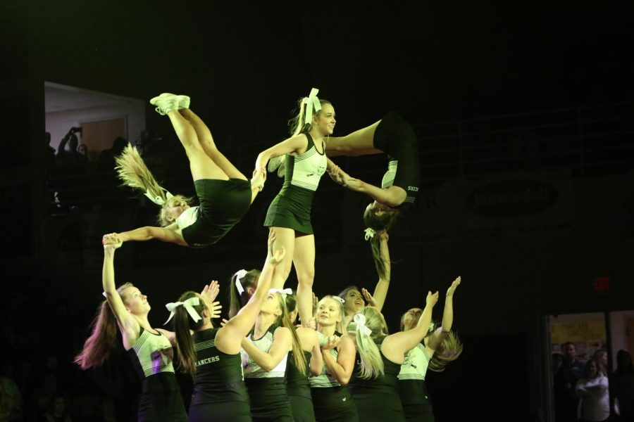 During a pep assembly, the varsity cheerleading squad performs their routine for the student body. This year, cheer, along with other performances will be performed and streamed virtually during homecoming week.