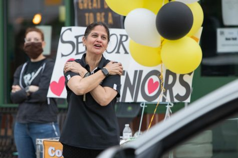 Watching as seniors leave the parking lot, Assistant Principal Kirti Mehrotra gives air hugs at the farewell parade held for the Class of 2020 on May 21.