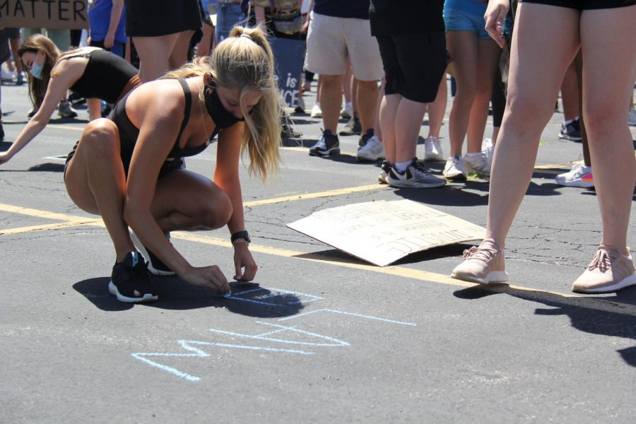 Class of 2019 graduate Maddie Williams writes in chalk on the blacktop of the Lafayette parking lot as part of the opening ceremony activities. For this activity, participants were asked to write one thing they want to see change in America.