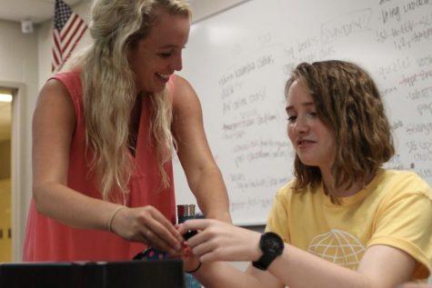 During former Latin teacher Emelia Osborne's Latin class, senior Brigid Ogle works on a breakout box project with the help of Osborne.