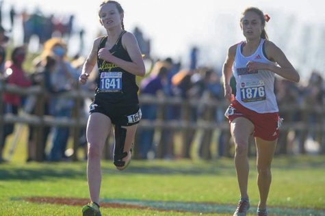 Sophomore Elissa Barnard runs alongside her Parkway West competitor in the Missouri State High School Activities Association (MSHSAA) Cross Country Competition. Barnard placed ninth in the competition, running the event with a time of 18:43.60. That time helped the Lady Lancers become State Champs for the third time in their history.