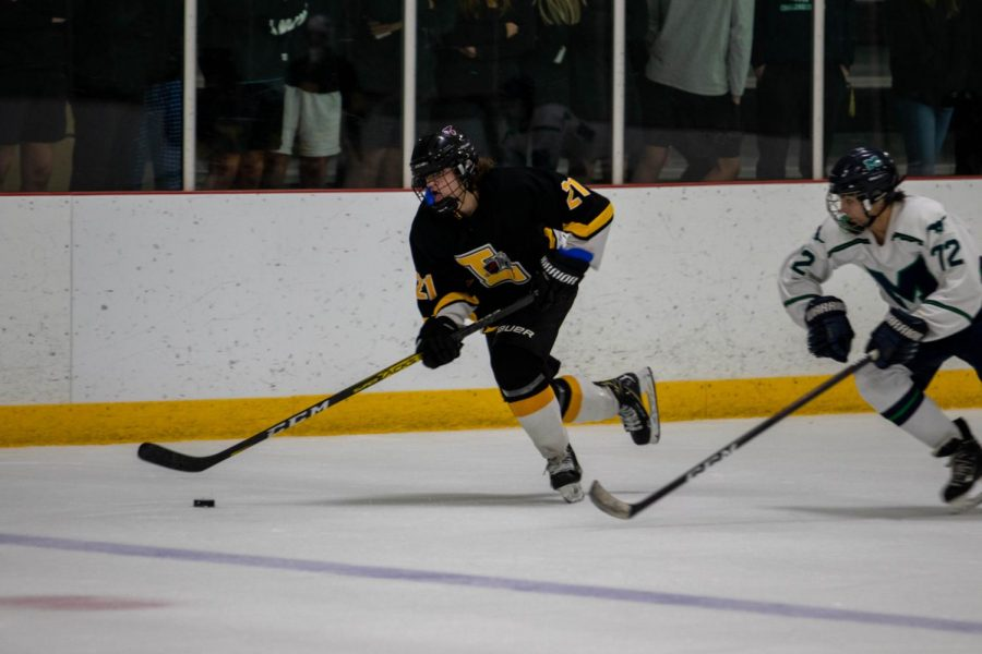Senior Ryan Duggan races down the side of the rink with the puck against a Marquette defender in a pre-season game. The Lancers won their first regular season game against Kirkwood High School, 4-2, and will play DeSmet on Dec. 4.