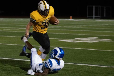 In a game against Ladue High School, senior Mitchel Hoffman runs over a defender. The Lancers won the game 44-38, and Hoffman had 138 rushing yards.