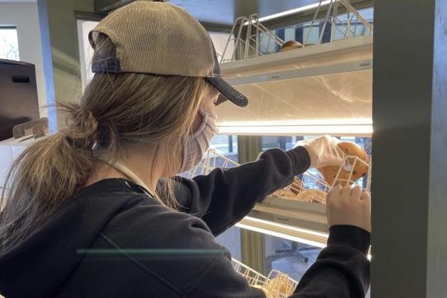 Junior Marissa Trottier restocks bagels during her morning shift at St. Louis Bread Company.