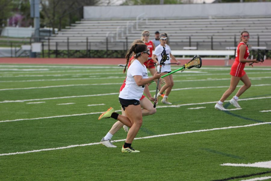 Senior+Mia+Simpson+swings+down+the+right+side+looking+for+an+open+teammate.+Simpson+scored+two+goals+in+the+13-9+victory+over+Cor+Jesu+on+April+12.