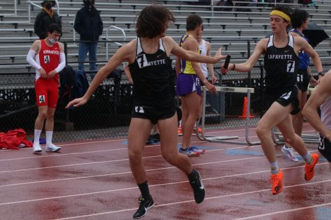 On a rainy morning at the Lafayette Track and Field Invitational,  junior Bross Miller passes the baton to senior Noah Kronauge in the 4x800 relay.