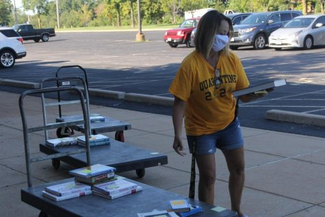 Class secretary Karen Barber helps distribute books and materials during the August 2020 date for Chromebook drop-off and material pick-up.
