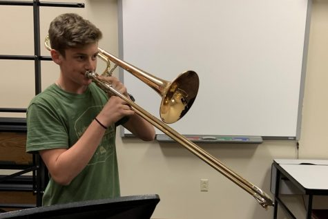 Senior Corban Leslie plays trombone after marching band rehearsal. Leslie has been playing trombone since seventh grade. In addition to the trombone, he plays five other instruments.