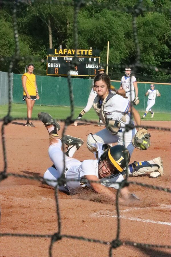 Sophomore Addyson Jones slides to home plate after a hit by junior Emma Durfee. After the slide, Jones was called out by the umpire. She holds the fourth-highest amount of plate appearances on her team with 17.