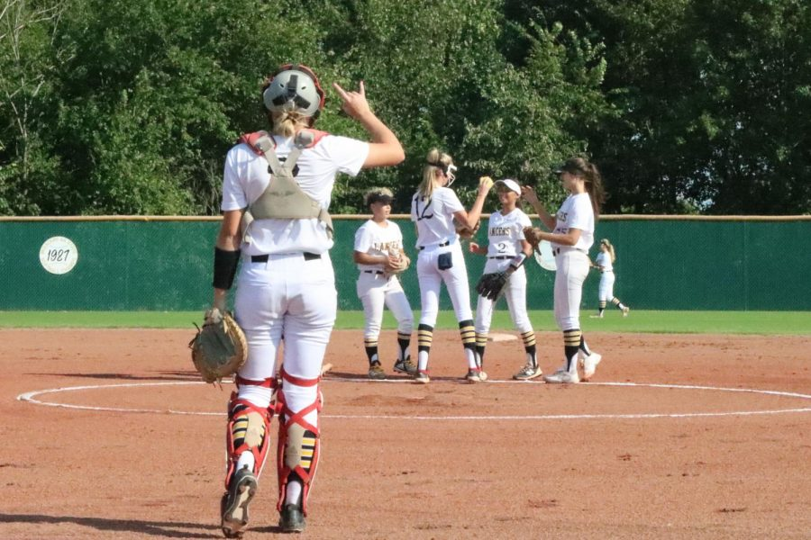 Junior Lily Ware signals the second out of the first inning as senior Gina Betancourt-Diaz, Carr, freshman Addison Penn and senior Kaley Adzick celebrate on the mound.